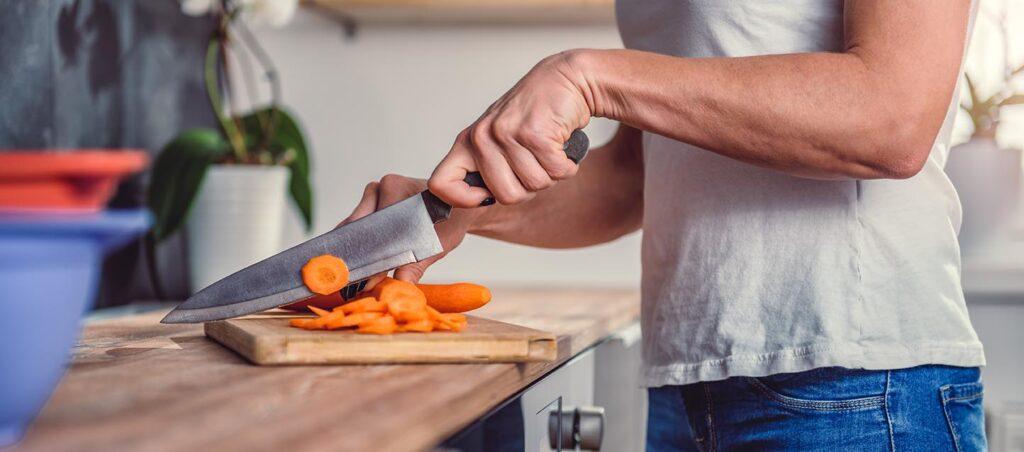 Vrouw is wortel aan het snijden